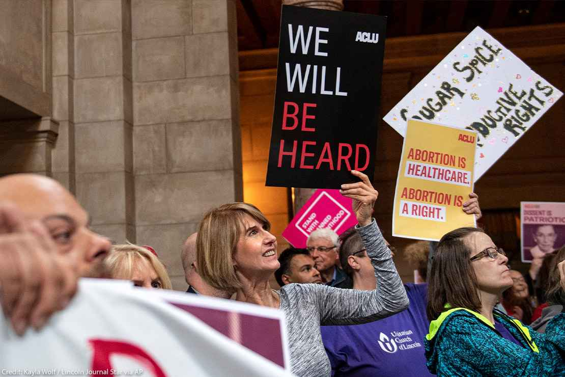 "Supporters of abortion-rights attend a reproductive freedom rally at state capitol in Nebraska, holding ACLU signs that read ""We will be heard"" and ""abortion is healthcare."""