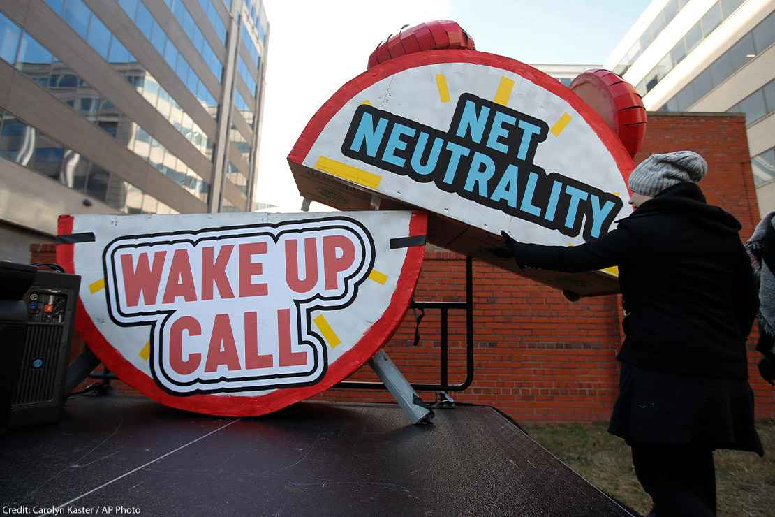 "Woman helps to dismantle a large alarm clock display that reads ""Net Neutrality Wake Up Call"" from the stage after a protest in front of the FCC in Washington, DC."