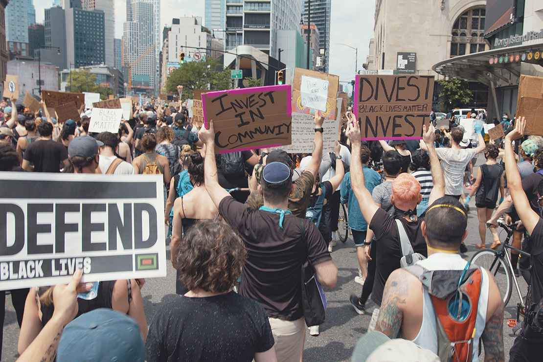 Protesters marching in a demonstration with signs calling on officials to divest from police and invest in communities.