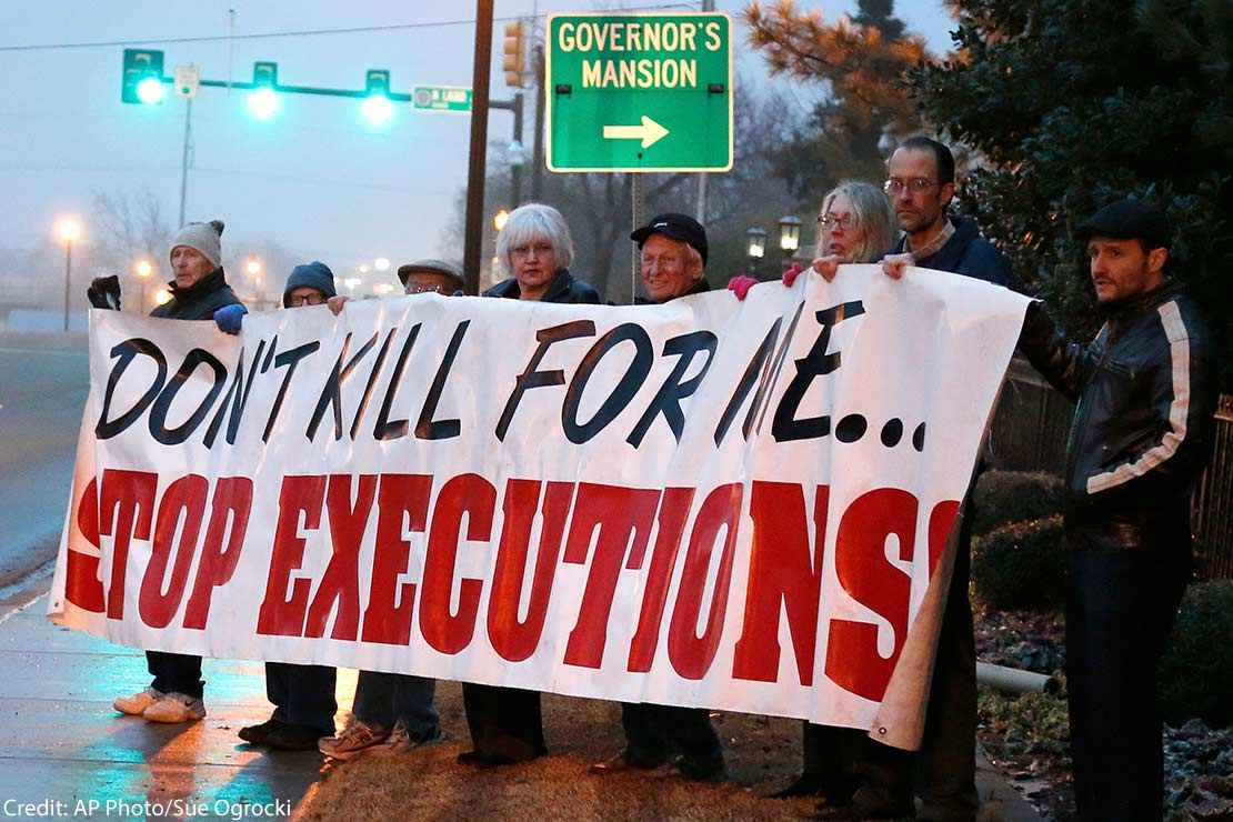 "Protestors holding a banner with the text ""Don't kill for me...Stop executions."""